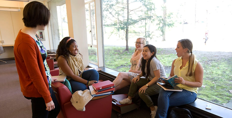 diverse group of students chatting in library by windows