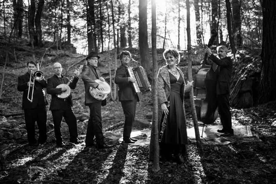 a black and white photo of the band Klezperanto standing in the forest