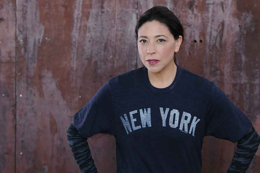 "image of a Tina D'Elia looking at the camera and wearing a blue sweatshirt with the words ""New York"" on it."