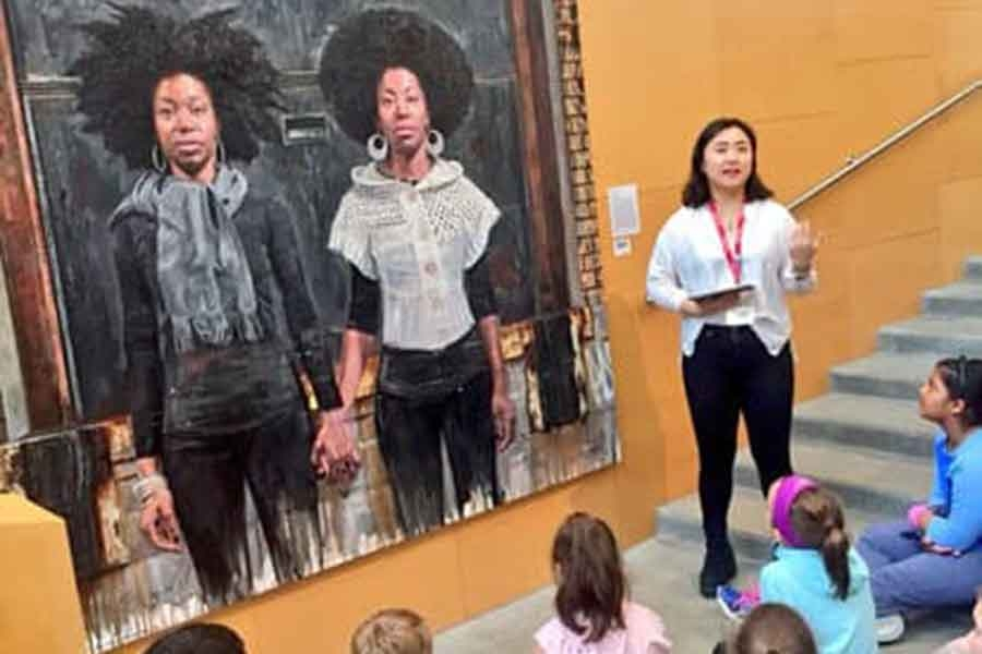 a student tour guide talking to a group of people and standing in front of a portrait painting of two black women