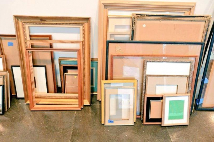 a variety of print frames leaning against a wall