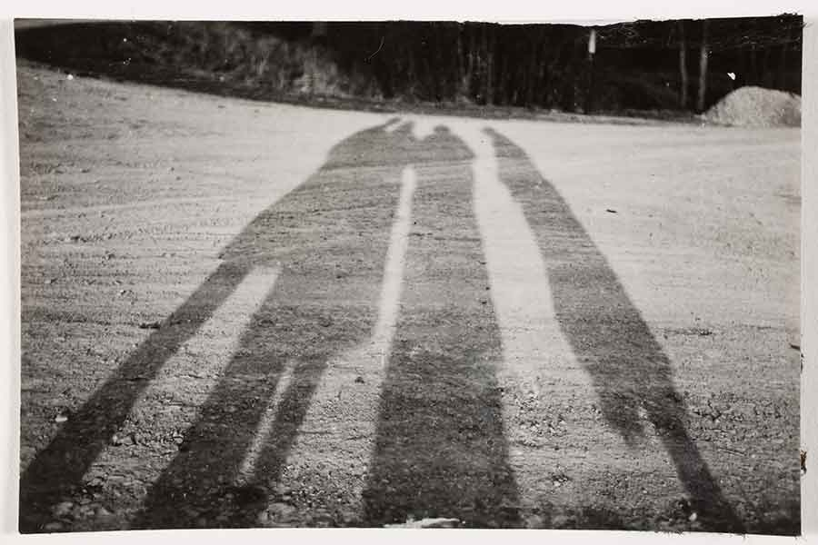 black and white image of three people's shadows on the ground
