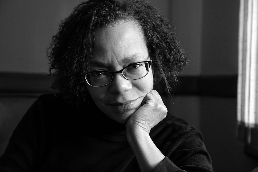black and white portrait of a woman wearing glasses and looking at camera