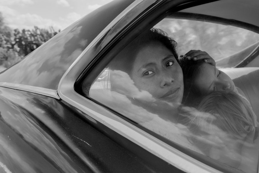 black and white image of a woman in car holding two children