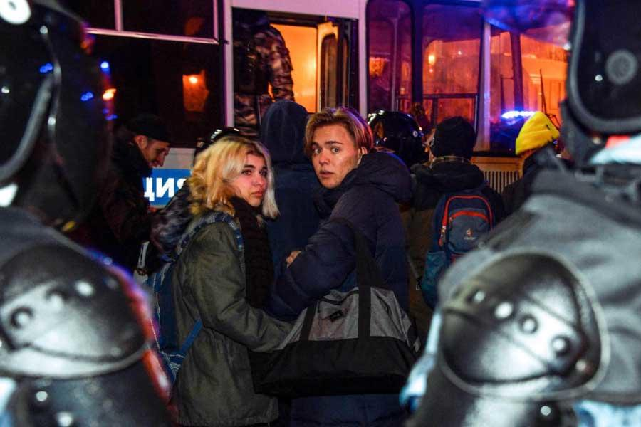 Riot police officers detain people during a protest in moscow