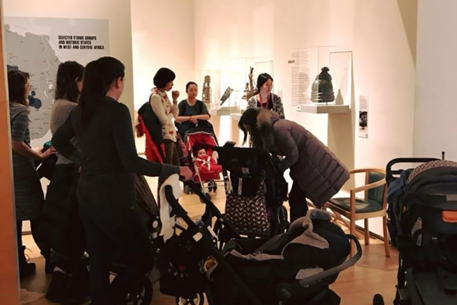 Families with children in strollers stand in a Davis museum gallery
