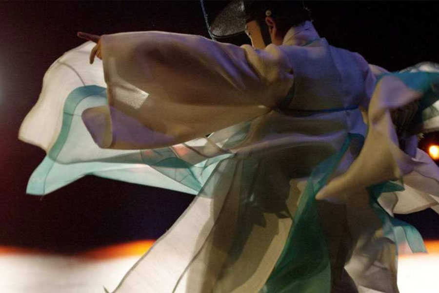a figure draped in light colored fabrics dancing against a black backdrop