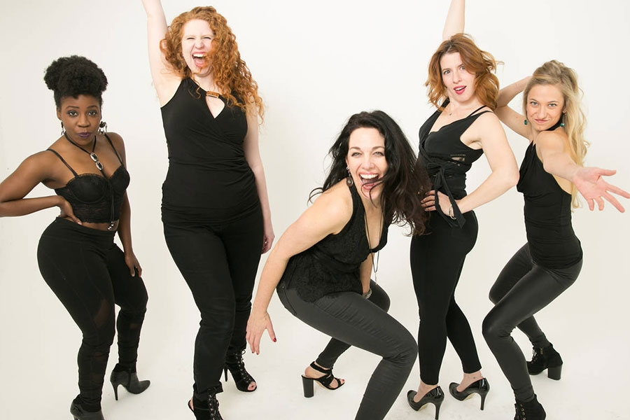 image of five women wearing black and making comedic gestures