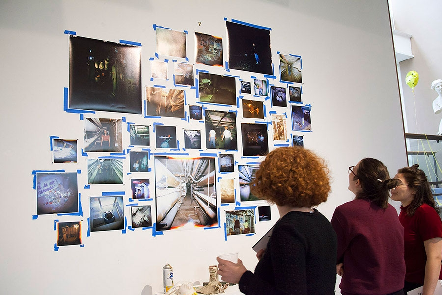 students looking at photographs taped to a wall