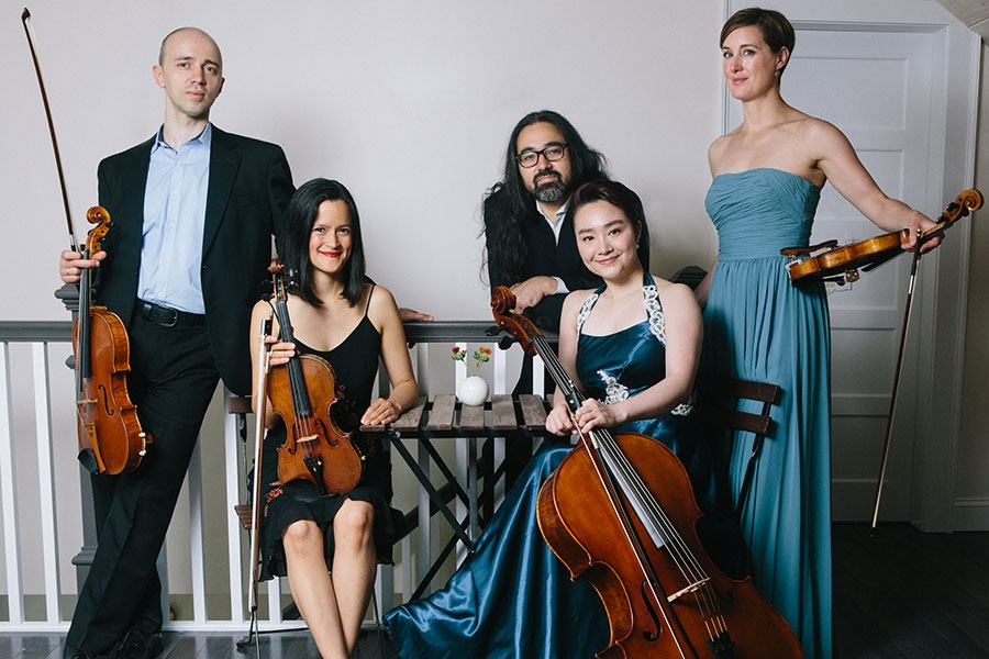 image of 5 adults in formal attire holding their instruments and looking at the camera