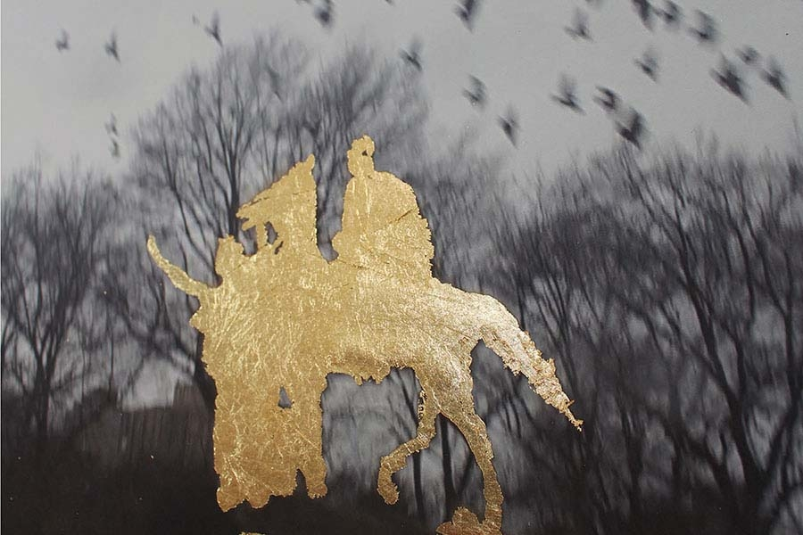 abstract gold silhouette seemingly of a person on a horse set against a black and white photograph of birds flying above trees