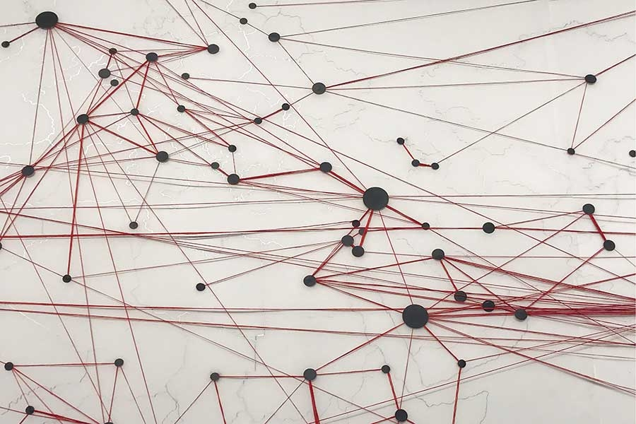 abstract art piece of red string strung between black dots.