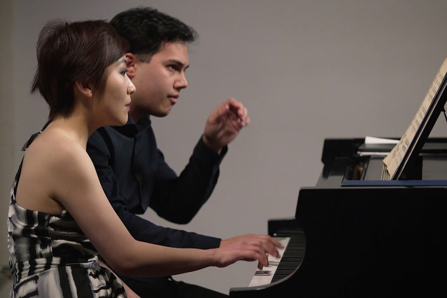 two people playing the piano together