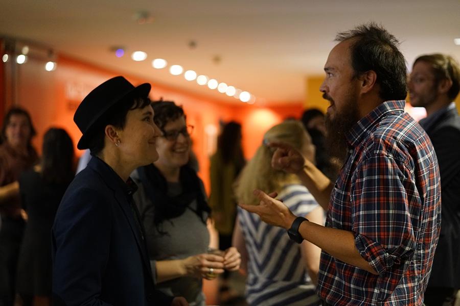 a man explains an artwork to two women