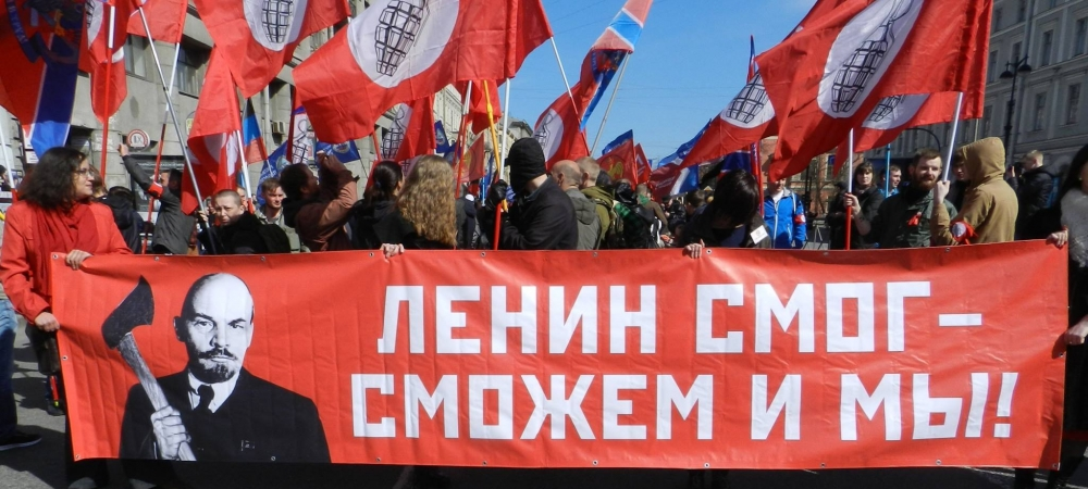 "Image of marchers holding sign that reads, ""Lenin could do it—so can we!"""