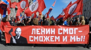 """Image of marchers holding sign that reads, """"Lenin could do it—so can we!"""""""