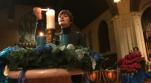 A student lights a candle at the Christmas Vespers ceremony.