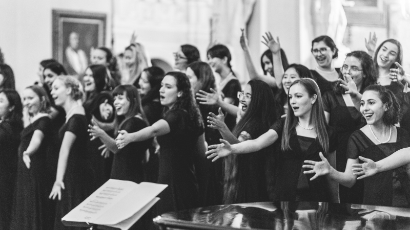 black and white photo of choir performing with hand motions