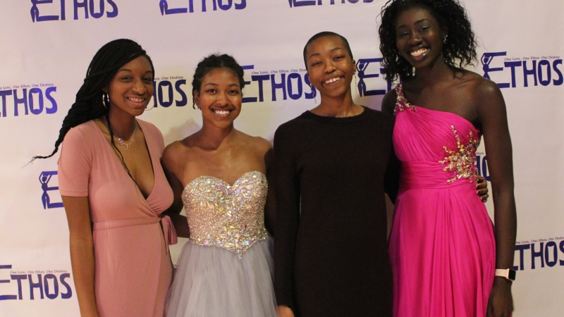 Four students standing in dresses for the Ethos gala