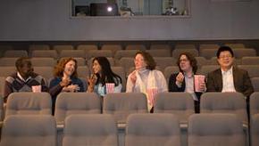 Pashington Obeng, Eve Zimmerman, Anjali Prabhu, Winnie Wood, Nick Knouf, and Mingwei Song seated in Collins cinema holding popcorn