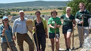 Burns and 5 students in green shirts hold excavation tools
