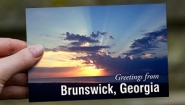 "Hand holds a postcard that reads ""Greetings from Brunswick, Georgia"""