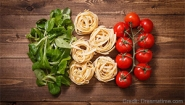 Basil leaves, pasta and tomatoes arranged to represent the Italian flag.