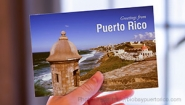 "Hand holds a postcard that reads ""Greetings from Puerto Rico"""
