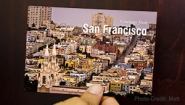 "Hand holds a postcard that reads ""greetings from San Francisco"""