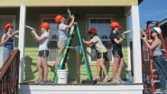 students work on porch of Habitat house