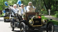 white haired alums wave from antique car