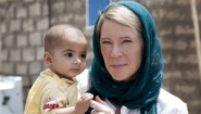 Carolyn Miles holding baby in Iraq