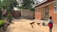 scene from Beatrice Achieng Nas video: girl with chickens