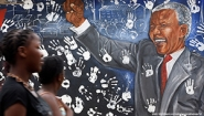 women walk in front of Mandela mural
