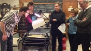 5 faculty and staff gather round old printing press