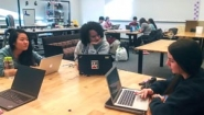 three students work at table with laptops