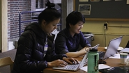 two students work at laptops