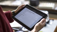 student holding iPad with survey waiting to be filled out