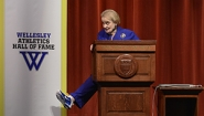 Albright shows off blue sneaker from behind podium