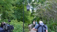Jane Pauley and Hillary Clinton stroll on footbridge near Lake Waban as crew films