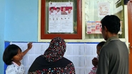 family reads poster at Indonesia polling place