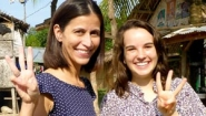 Ami Swanepoele '02 and Victoria Rines '15 make a three-fingered Wellesley W sign