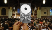 hand holding b&w image of 1970s Flower Sunday in front of full color image of modern flower sunday, both inside Chapel