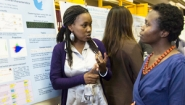 student researcher explains findings to visitor
