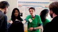 three Wellesley students in green t-shirts explain their software to onlookers