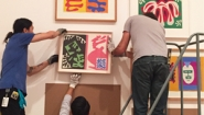 Two museum workers mount Matisse painting among others on wall