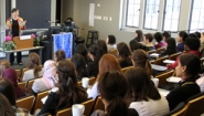 Katherine Marshall lecturing, seen from behind rows of students