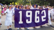 alumnae dressed in white carry the purple banner of the class of 1962