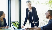 older woman executive leads meeting with two younger colleagues