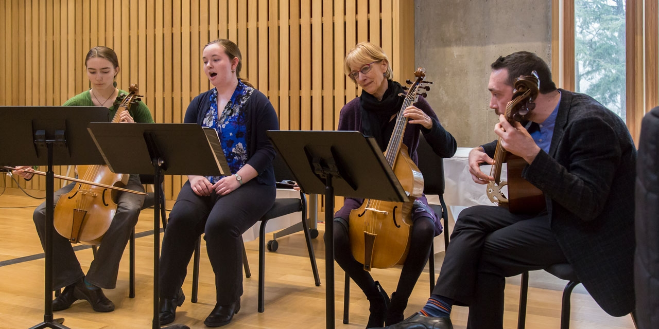 Two students and two professors play musical instruments on a stage.